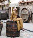 Het meisje in een nationaal kostuum zit op een groot vat, is de reclame Stock Foto