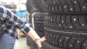 Het meisje in een plaidoverhemd kiest de winterbanden voor een auto in een winkel stock video