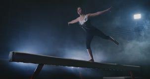 Het meisje is een professionele atleet uitvoert gymnastiek- acrobatische truc op een straal in backlight en langzame motie in spo stock footage