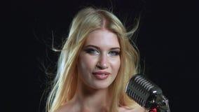 Het meisje in een rode kleding zingt in een retro microfoon Zwarte achtergrond Sluit omhoog stock video