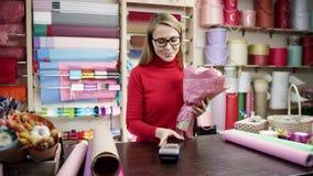 Het meisje in een rode verbindingsdraad geeft de terminal voor het paing aan de koper, hij die de kaart vastmaken aan de terminal stock video
