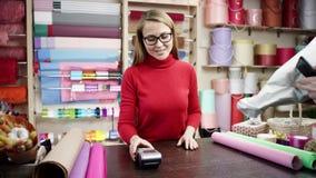 Het meisje in een rode verbindingsdraad geeft de terminal voor het paing aan de koper, hij die de kaart vastmaken aan de terminal stock videobeelden
