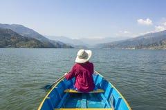 Het meisje in een rood overhemd en een witte hoed zit in een blauwe houten boot met een peddel in haar handen, op een meer tegen  stock foto's
