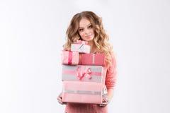 Het meisje in een roze blouse die roze dozen met giften op een witte achtergrond houden Stock Afbeelding
