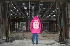 Het meisje in een roze jasje met een rugzak bevindt zich in een verlaten oud pakhuis Stock Foto