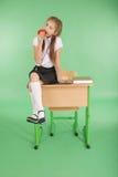 Het meisje in een school eenvormige zitting op bureau en eet appel Stock Foto