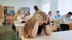 Het meisje is een schoolmeisje die in klasse schreeuwen en haar klasgenoten troosten haar stock foto