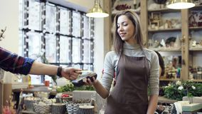 Het meisje in een schort geeft de terminal voor het paing aan de koper, hij die de kaart vastmaken aan de terminal en betaalt stock footage