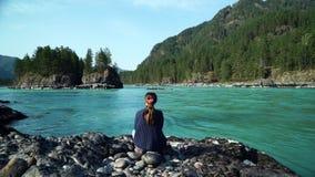 Het meisje in een sweater zit door de bergrivier Mooi landschap Achter mening stock videobeelden