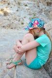 Het meisje in een turkooise kleding zit Stock Foto