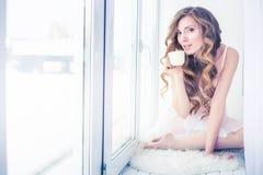 Het meisje in een wit jasje houdt de mok. Royalty-vrije Stock Afbeeldingen