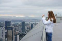Het meisje in een wit jasje met lang haar neemt een foto op de telefoon royalty-vrije stock foto's