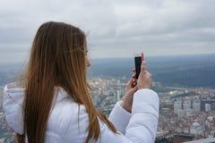 Het meisje in een wit jasje met lang haar neemt een foto op de telefoon royalty-vrije stock afbeeldingen