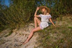 Het meisje in een witte kleding en in een strohoed zit op het strand door de rivier royalty-vrije stock afbeelding
