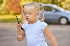 Het meisje in een witte kleding wordt verloren in de stad en telefoneert haar ouders royalty-vrije stock fotografie
