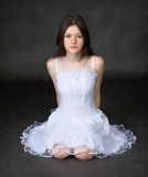 Het meisje in een witte kleding zit op een zwarte achtergrond Royalty-vrije Stock Foto