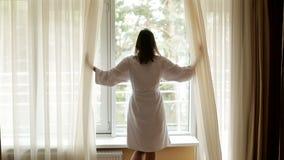Het meisje in een witte robe komt uit uit de linkerkant stock videobeelden