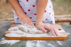 Het meisje in een witte schort bereidt het deeg op een scherpe raad voor stock afbeeldingen