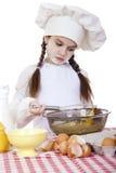 Het meisje in een witte schort en de chef-kokshoed kneden het deeg in Th Stock Fotografie