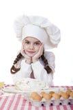 Het meisje in een witte schort en de chef-kokshoed kneden het deeg in Th Stock Foto's