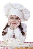 Het meisje in een witte schort en de chef-kokshoed kneden het deeg in Th Stock Foto