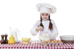 Het meisje in een witte schort en de chef-kokshoed kneden het deeg in Th Royalty-vrije Stock Foto's