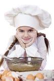Het meisje in een witte schort en de chef-kokshoed kneden het deeg in Th Stock Afbeelding