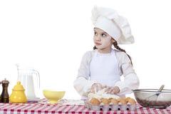 Het meisje in een witte schort en de chef-kokshoed kneden het deeg in Th Royalty-vrije Stock Fotografie