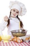 Het meisje in een witte schort en de chef-kokshoed kneden het deeg in Th Royalty-vrije Stock Afbeelding