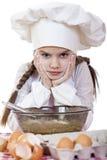 Het meisje in een witte schort en de chef-kokshoed kneden het deeg in Th Stock Afbeeldingen