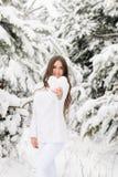 Het meisje in een witte warme sweater in een de winterbos houdt een hart Fr stock foto
