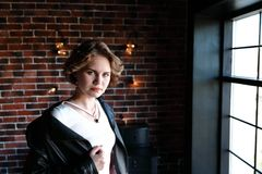 Het meisje in een zwart jasje en een lichte die blouse stelt tegengesteld aan een venster, een achtergrond de bakstenen muur met  stock afbeeldingen