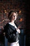Het meisje in een zwart jasje en een lichte die blouse stelt tegengesteld aan een venster, een achtergrond de bakstenen muur met  stock foto's
