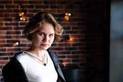 Het meisje in een zwart jasje en een lichte die blouse stelt tegengesteld aan een venster, een achtergrond de bakstenen muur met  stock fotografie