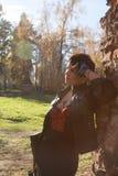 Het meisje in een zwart jasje stelt in openlucht Stock Foto's
