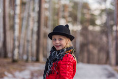 Het meisje in een zwarte hoed met oren en Pavloposadskiye-sjaal loopt in de dag van de park koude lente Stock Afbeeldingen