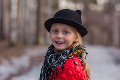 Het meisje in een zwarte hoed met oren en Pavloposadskiye-sjaal loopt in de dag van de park koude lente Royalty-vrije Stock Fotografie