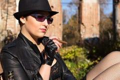 Het meisje in een zwarte hoed rookt een sigaar Royalty-vrije Stock Afbeeldingen