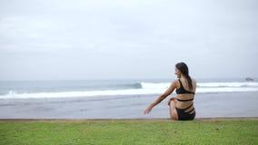Het meisje in een zwempak bekijkt de golven stock footage