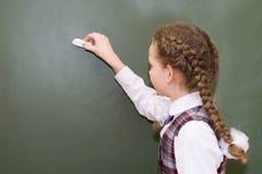 Het meisje in eenvormige school schrijft met krijt op bord stock afbeeldingen