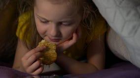 Het meisje eet bij nacht stock videobeelden