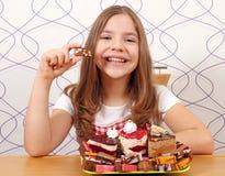 Het meisje eet cake Stock Afbeeldingen