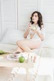 Het meisje eet cake voor Ontbijt in bed stock fotografie