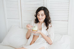 Het meisje eet cake voor Ontbijt in bed stock foto