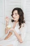 Het meisje eet cake voor Ontbijt in bed stock foto's
