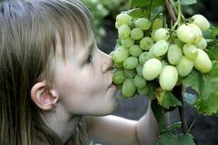 Het meisje eet de druif Stock Afbeeldingen