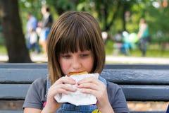 Het meisje eet in de straten stock afbeelding