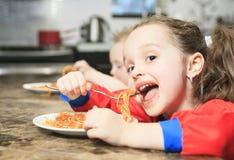 Het meisje eet deegwaren in de keukenlijst royalty-vrije stock afbeeldingen