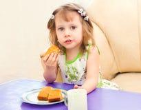 Het meisje eet een pasteistuk Stock Foto