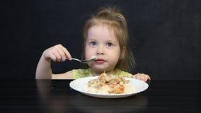 Het meisje eet en laat vallen voedsel stock video